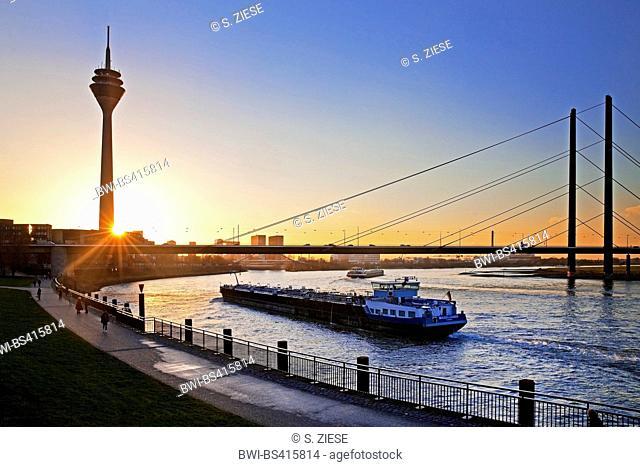 transport ship on Rhine river, Rheinturm and Rheinkniebruecke at sunset, Germany, North Rhine-Westphalia, Duesseldorf