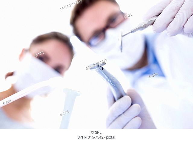 MODEL RELEASED. Dentist and dental assistant conducting dental operation