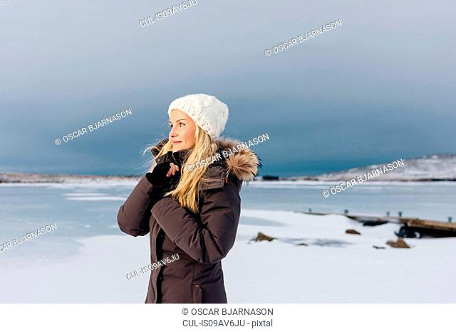 Side view of mid adult woman on frozen landscape looking away smiling