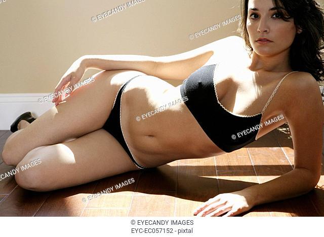 Woman lying on the floor in underwear