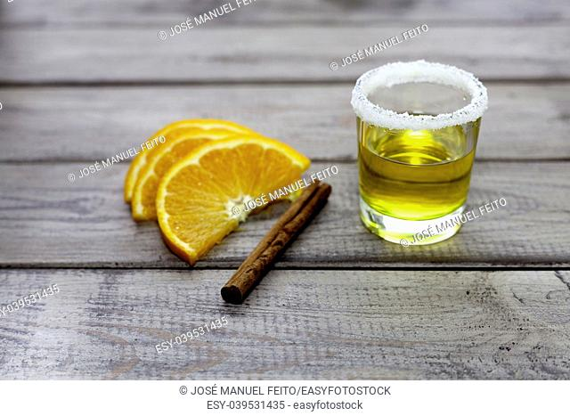 tequila shot with orange slice and cinnamon on wood background