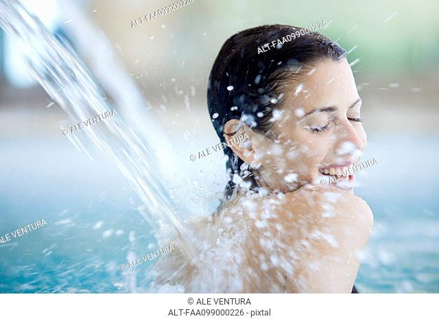 Woman relaxing under fountain in pool