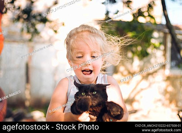 happy little girl playing with kitten