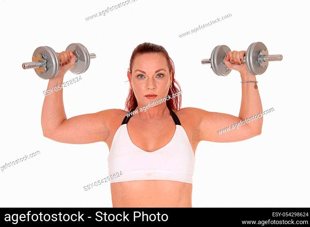 An exercising pretty woman standing in a sports bra and lifting.up the two dumbbells in her hand, isolated for white background