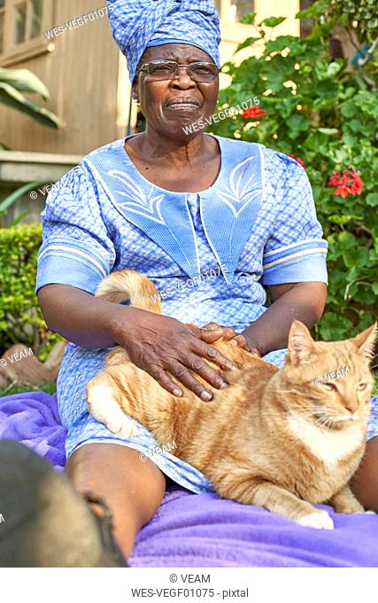 Senior woman with a cat sitting on a blanket in garden