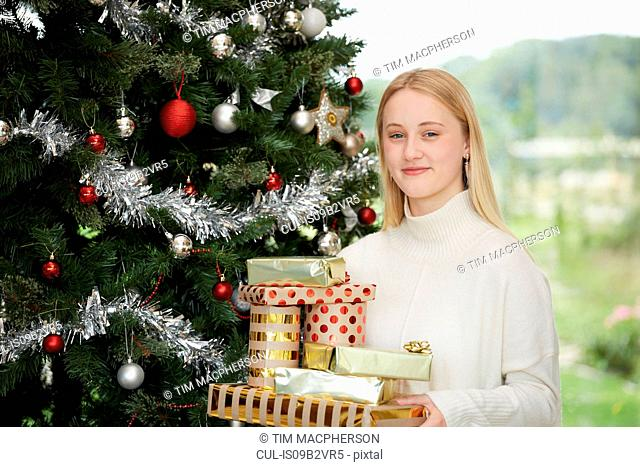 Portrait of teenage girl holding stack of chrismas presents by christmas tree