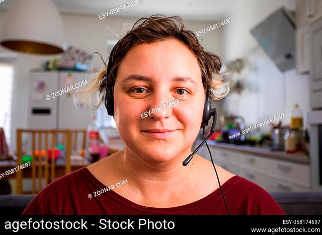 Portrait of young attractive woman in headphones while her conference call. Teacher providing online lessons while quarantine