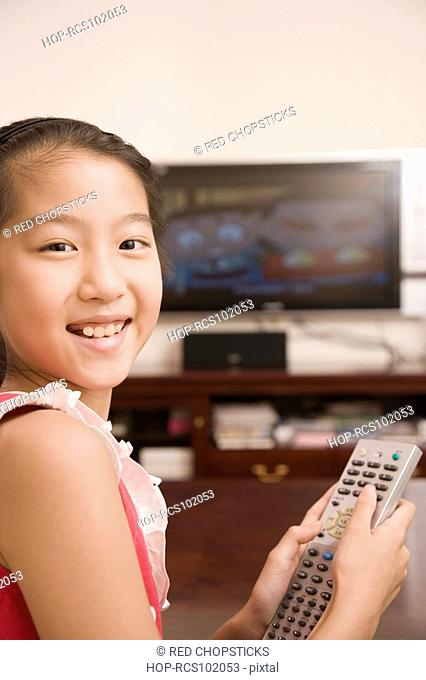 Portrait of a girl holding a remote control and smiling