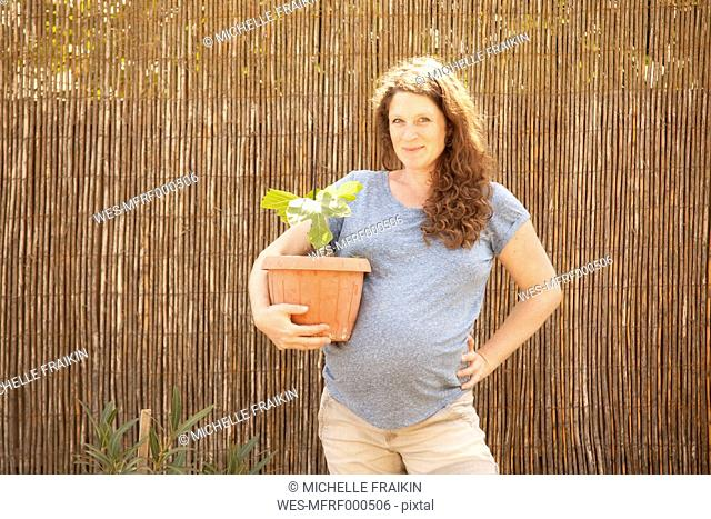 Portrait of smiling pregnant woman holding seedling in flowerpot