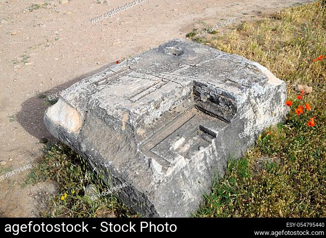 Fragments of ancient buildings, the ruins of the ancient city of Hierapolis. Stone blocks with traces of stone machining
