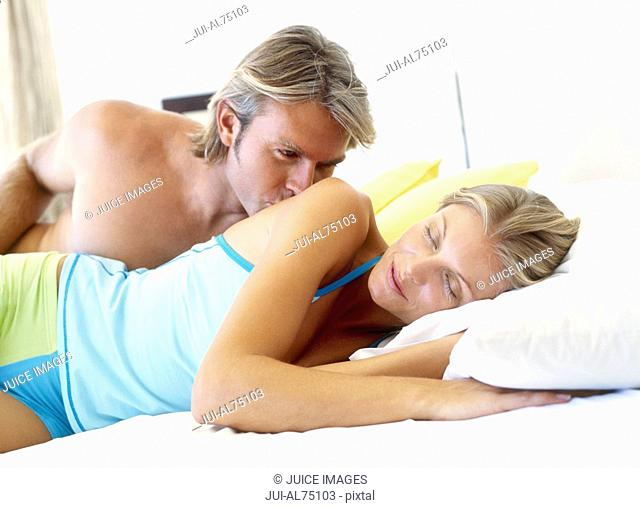 Portrait of a young man kissing his sleeping girlfriend's shoulder