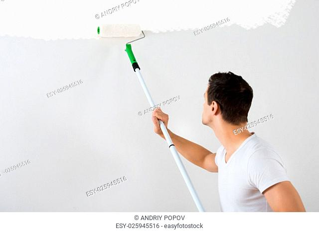 Side view of young man painting wall with paint roller at home