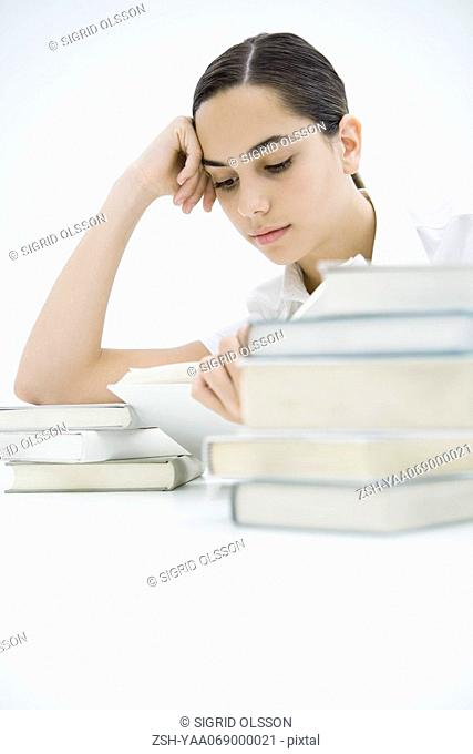 Female reading book, surrounded by two stacks of books, leaning on elbow