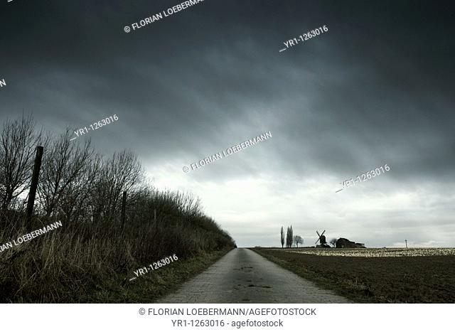 Landscape with an old windmill during winter. Dramatic sky. Shot in North Rhine-Westphalia, Germany