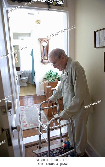 Feeble senior man standing with walker in doorway