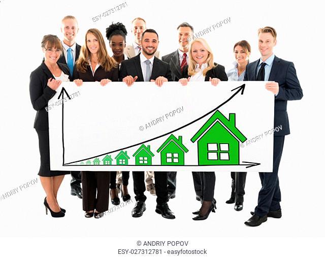 Portrait of confident multi ethnic business team holding blank billboard against white background