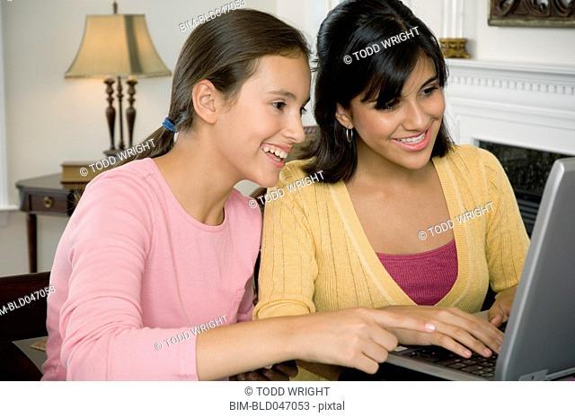 Multi-ethnic girls looking at laptop