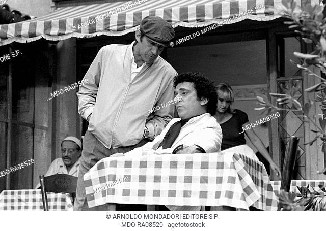 Italian actor Walter Chiari (Walter Annichiarico) beside Italian actor Gianni Cavina sitting at the table in a restaurant in the film Passi furtivi in una notte...