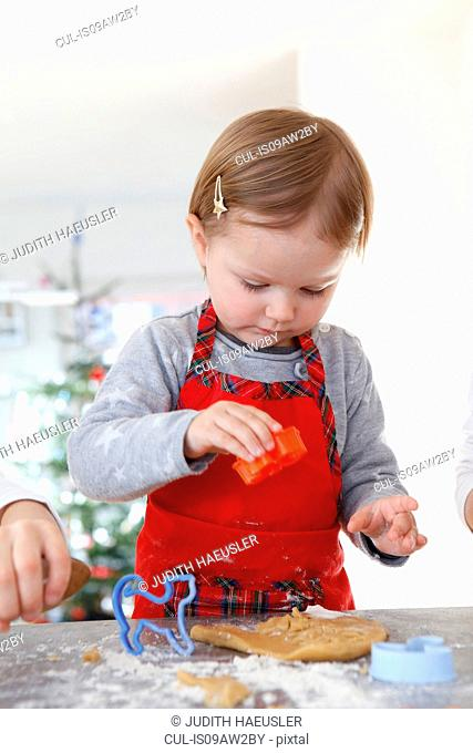 Girl wearing apron looking down using cookie cutter