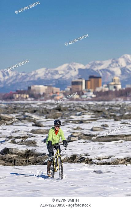 A young woman rides her studded tire bicycle amongst the ice chunks in the Cook Inlet next to the Tony Knowles Coastal Trail, Anchorage, Southcentral Alaska