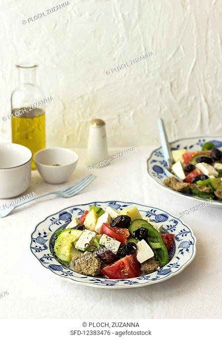 Tomato and cucumber salad with zucchini, potato, green pepper, black olives, oregano and farmhouse bread (Crete)