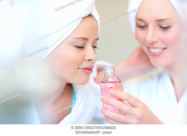 Young women in spa inhaling aromatherapy products