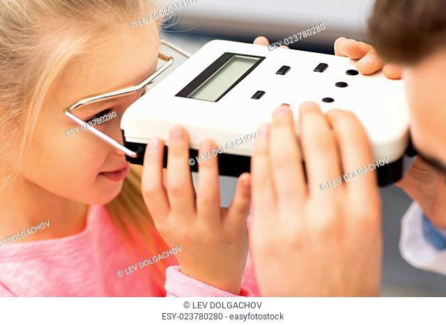 health care, medicine, people, eyesight and technology concept - close up of optometrist with pupillometer checking patient intraocular pressure at eye clinic...