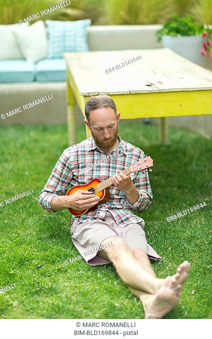 Caucasian man playing ukulele in backyard