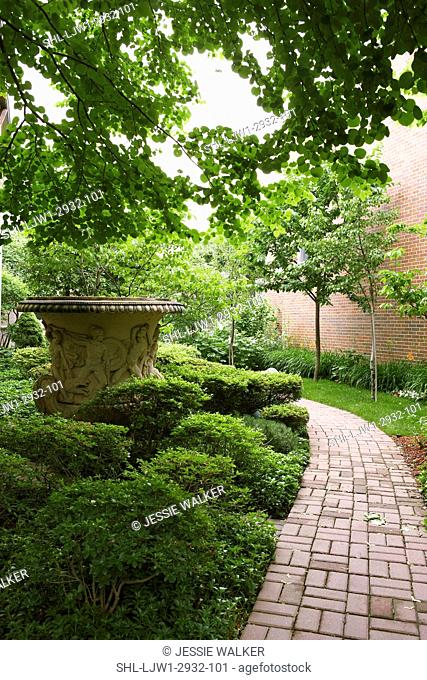 GARDENS: Basketweave brick walkway, six foot tall urn decorated with a frieze of classical warriors,s its in the side yard, trees and rhododendron