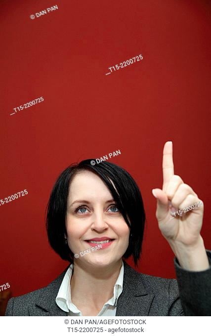 A black haired young woman pointing her finger up