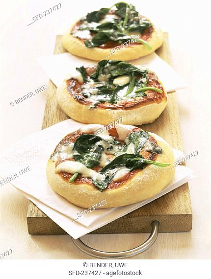 Mini-pizzas with spinach on wooden chopping board