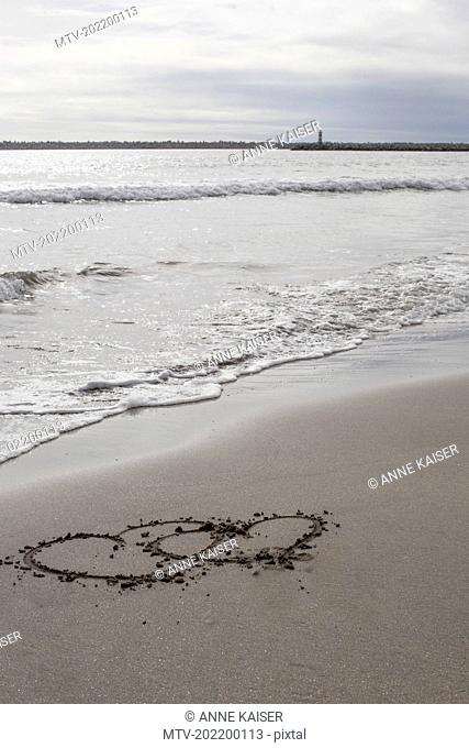 Two heart shape drawn in sand on the beach, Viana do Castelo, Norte Region, Portugal