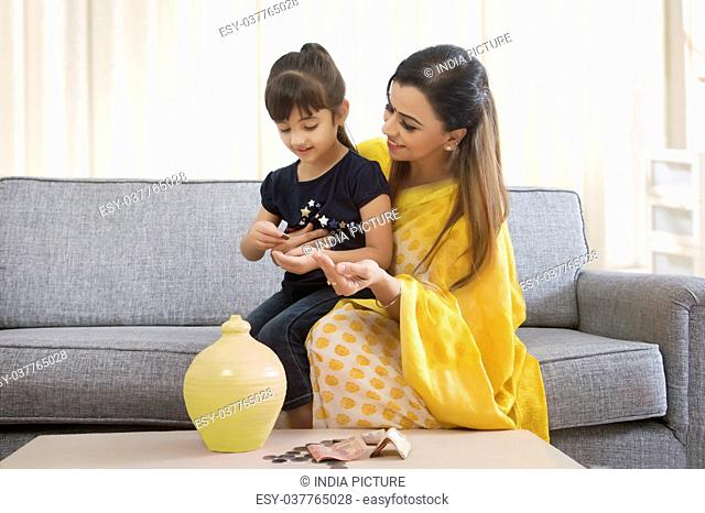 Mother and daughter inserting coins in clay piggy bank