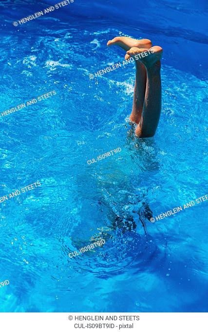 Girl doing handstand in outdoor swimming pool, legs and feet out of water, Vernazza, Liguria, Italy