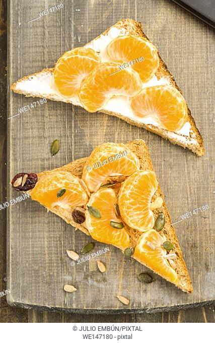 mandarin oranges and pine nuts on wholemeal bread triangles on wood