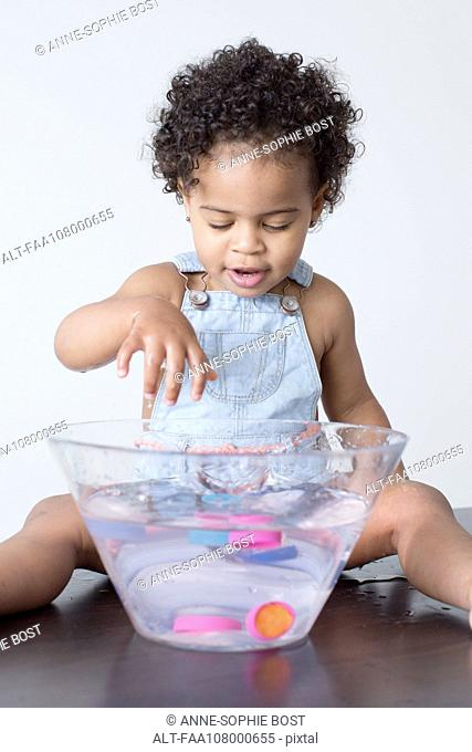 Toddler girl playing with toys in bowl of water