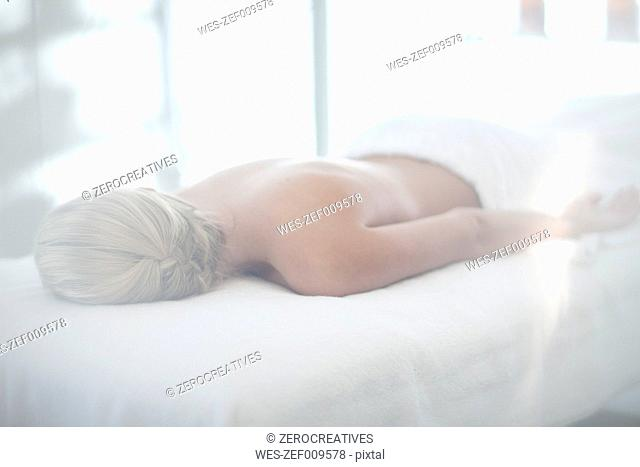 Young woman lying on lounge at spa