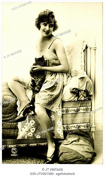 French Lingerie Model Seated on Edge of Bed Holding Cat, Circa 1920