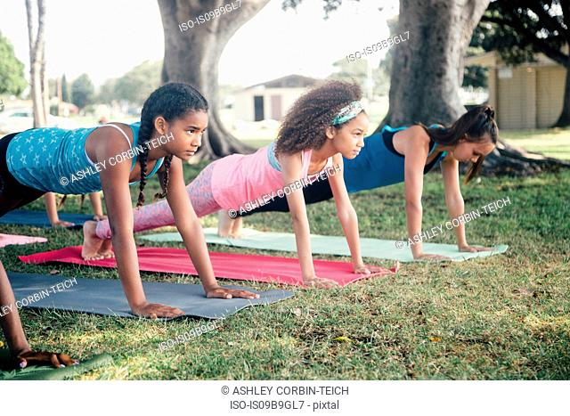 Girls and teenage schoolgirls practicing yoga plank pose on school playing field
