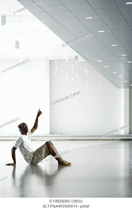 Teenage boy sitting on the floor, listening to headphones, pointing up