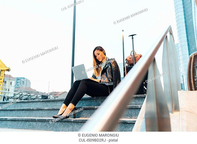 Businesswoman, sitting outdoors on steps, using laptop, luggage beside her, low angle view