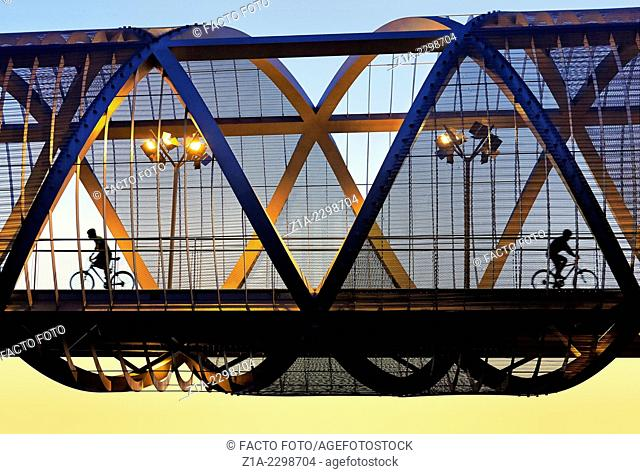 Two cyclists passing by the Arganzuela bridge, designed by architect Dominique Perrault. Madrid Rio Park. Madrid. Spain