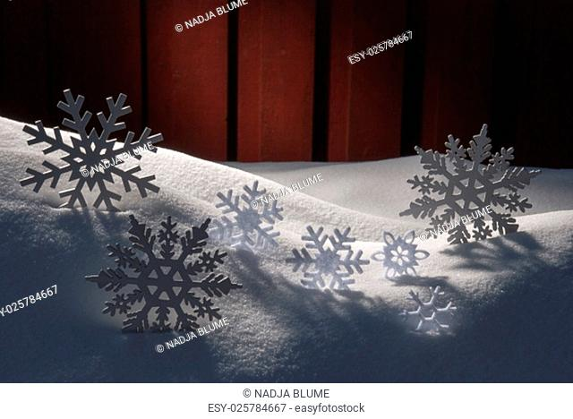 Four White Snowflakes On Snow. White Snowy Scenery As Christmas Decoration. Christmas Time Or Advent. Red Wooden Background