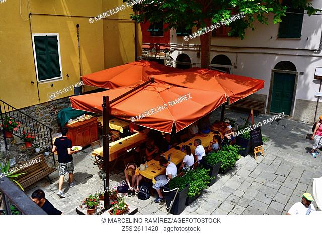 People eating traditional italian food in outdoor restaurant of Corniglia. Vernazza, Cinque Terre, La Spezia, Liguria, Italy