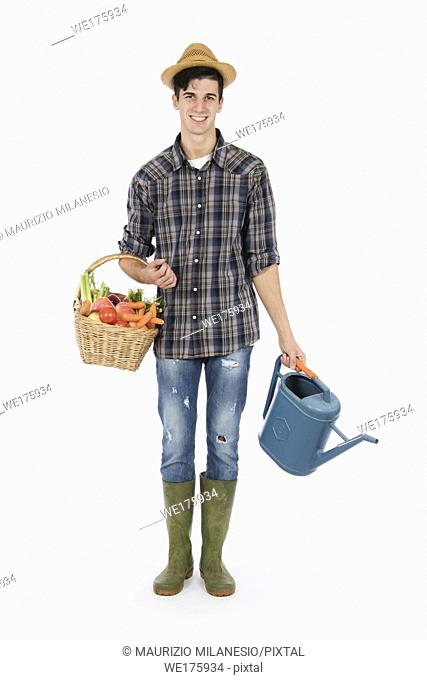 Young farmer with one arm holding a basket with fruit and vegetables, with the other a raincoat, he wears a straw hat, checked shirt and green rubber boots
