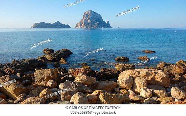 The small island of Es Vedrà seen from a rock beach in Ibiza island. Spain, Balearic islands, Spain, Europe