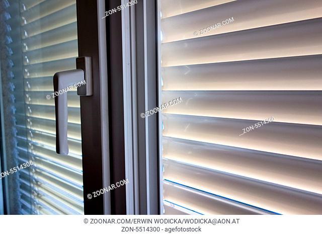 Zum Schutz gegen Hitze und Sonne werden an einem Fenster Jalousien angebracht