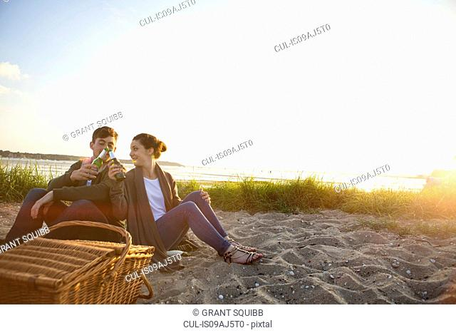 Young couple picnicing on Bournemouth beach, Dorset, UK