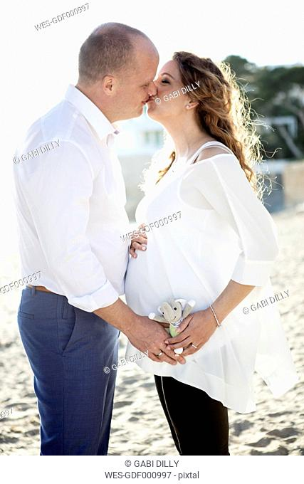 Spain, Majorca, pregnant woman kissing man on beach