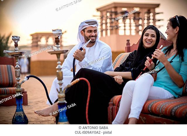 Local couple wearing traditional clothes smoking shisha on sofa with female tourist, Dubai, United Arab Emirates